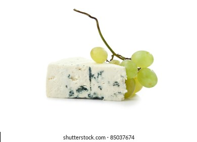 wedge of gorgonzola decorated with grapes isolated on white background