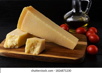 Wedge of italian hard cheese Grana Padano or Parmesan on a brown wood cutting boad, small red tomatoes and olive oil over black wood table. Low key image. Front view.