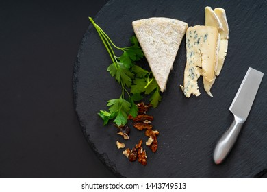 Wedge of semi-soft cheese on a round black board with chopped walnuts and fresh parsley garnish viewed from above with copy space