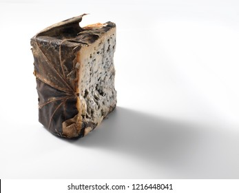 A wedge of soft, Spanish, Valdeon Cabrales, blue cheese, wrapped in sycamore maple or chestnut leaves, with contact shadow, isolated on white background