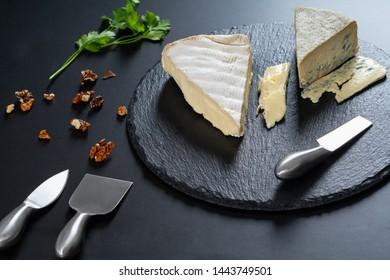 Wedges of semi-soft cheese on a black wooden cheese platter with steel cutter and scattered chopped walnuts in a high angle food still life