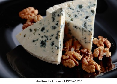 Wedges of soft blue cheese with walnuts on a black plate.