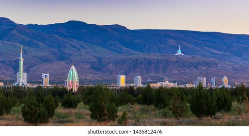 Wednesday, 26 June 2019; Ashgabat, Turkmenistan; Beautiful cityscape, panorama view on the white city at blue mountains with iconic landmarks of the capital of Central Asian state few minutes sunset.