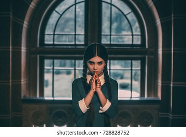 Wednesday Addams. Angry girl student after the exam with bloody hands. Gothic look for a Halloween party.Creative colors.The background of the old castle window