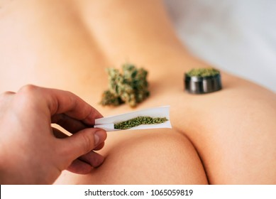 Weed and Cannabis buds grinder and not rolled joint on the girl's ass. The concept of sex and marijuana. themed weed and sex