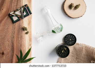 Weed pouch, cannabis grinder, marijuana pipe and buds on top of a wooden surface and white background.