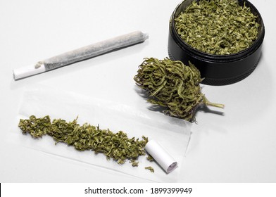 weed smoker kit of grinder full of dry herb and joint with medical marijuana with paper filter and piece of rolling paper on white background
