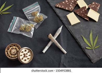 Weed and sweets: joints, marijuana leaves, buds on plastic bag and grinder accompanied with different types of chocolate on black textured background.