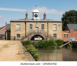 Weedon, Northamptonshire / UK - July 10th 2018: Brick built East Lodge of Weedon's former Ordnance Depot stands at the end of a waterway. Its white clock tower stands above stairs leading to a door.