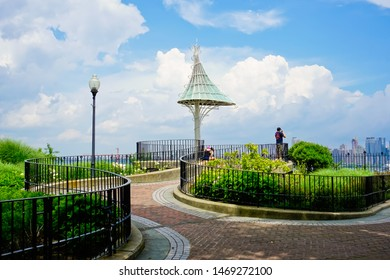 Weehawken, New Jersey/United states-7/6/2019: scenic landscape design with curved iron fence, garden, and pavilion in Hamilton park with the background of cityscape of Manhattan
