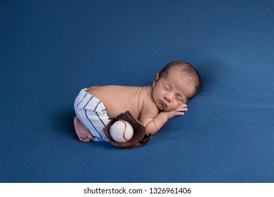 A week old, sleeping, newborn baby boy wearing baseball uniform pants with a catcher's mitt and ball.