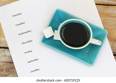 Weekdays listed on white paper and cup of black coffee