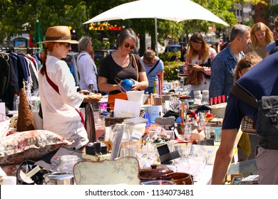 Weekend flea market jumble sale in the city center on a sunny day. Market booth with objects for sale and People are looking for a good find. Copenhagen, Denmark - July 14, 2018