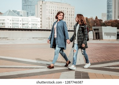 Weekend jaunt. A mother and a daughter walking at the city center together
