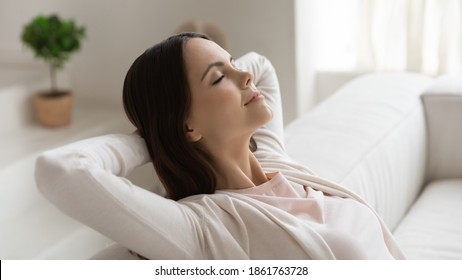 Weekend at least! Tranquil peaceful millennial female enjoying freedom dreaming relaxing on couch with closed eyes, hands behind head. Woman meditating breathing fresh air feeling happy