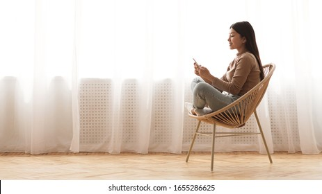 Weekend leisure. Girl using smartphone, sitting in wicker chair against window, panorama with free space