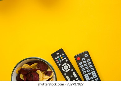 Weekend, leisure and hobby concept. a bright one-colore yellow background with a bowl with potato and beetroot chips and remote controls. Space for your text or product display