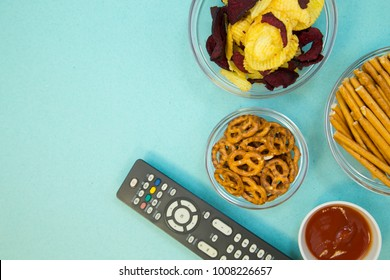 Weekend, Leisure, Lifestyle Concept. Evening in front of tv with a remote control, pretzels, chips and bread sticks on a light blue background, flat lay