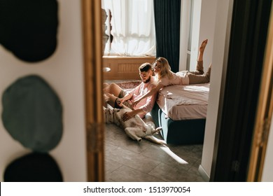 Weekend photo of couple playing with Labrador in sunny bedroom. Guy and girl are stroking belly of big dog