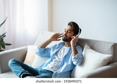Weekend Rest. Young arab guy in wireless headphones listening audiobook at home, calm eastern man sitting with closed eyes on couch in living room, enjoying domestic leisure, free space