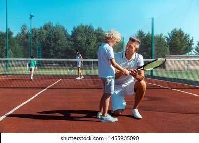 Weekend with son. Happy father smiling while enjoying weekend with his son while playing tennis