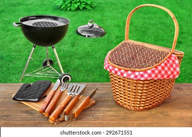 Weekend Summer Outdoor  BBQ Grill Party Ot Picnic Conceptual Scene With Picnic Wood Table, BBQ Tools, Hamper And Open Grill Appliance On The Backyard Lawn In The Background