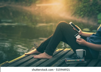 Weekend trendy lifestyle. Woman using phone for on line shopping and another hand holding credot card while sitting outdoor in morning. electronic business payment concept with vintage filter effect