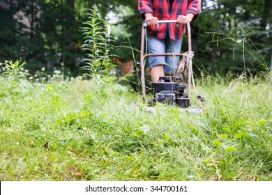 Weekend warrior hacks through a field of weeds, trying to get the lawn back under control at the cottage, using an ancient old lawnmower