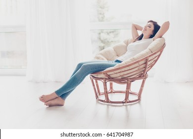 Weekends finally! Relaxed brunette girl is sitting on modern chair near the window in light cozy room at home. She is enjoying peace and morning