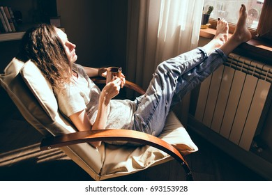 Weekends finally. Woman in blue jeans relaxing with cup of tea in armchair at home, daydreaming. Girl enjoying life, bright sunlight and heat from radiator. Cozy home. Heating season. Mortgage concept