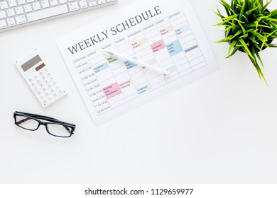 Weekly schedule of manager, office worker, pr specialist or marketing expert. Table with multicolored blocks on white office desk with computer, glasses, calculator top view copy space