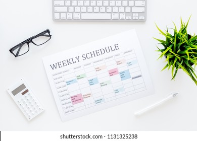 Weekly schedule of manager, office worker, pr specialist or marketing expert. Table with multicolored blocks on white office desk with computer, glasses, calculator top view