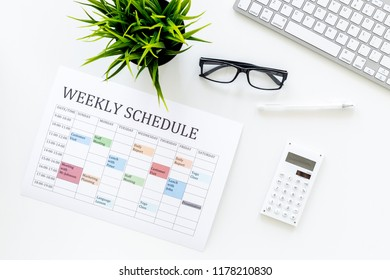 Weekly schedule. Planning the week. Multicolored planner on manager, marketologist's white office desk with computer keyboard and calculator top view