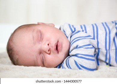A week-old baby boy (African and Caucasian ethnicities) sleeps peacefully on his stomach, facing the camera. Isolated closeup cropped to include upper torso and head. Neutral blanket and background.