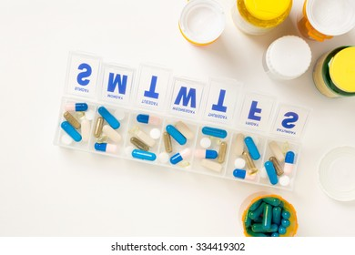 Weeks supply medicine organizer with pill bottles shot from above.