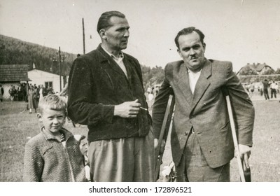 WEGIERSKA GORKA, POLAND, CIRCA FORTIES - Vintage photo of men (one of them with orthopedic sticks) and a boy
