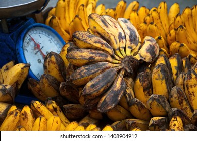 Weighing scale and pile of saba bananas for sale by a street vendor