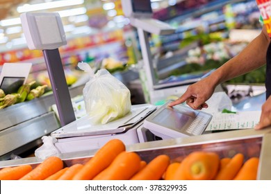 weighing of vegetable on electronic scales in supermarket.