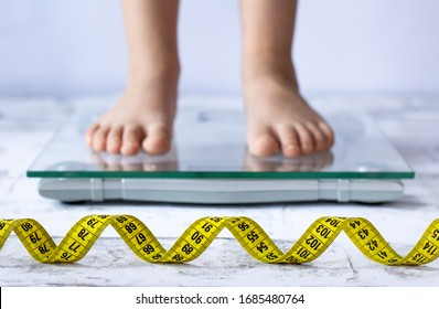 Weight control concept with centimeter in focus and blurred kid's feet on digital scale in the background. Child measuring weight, healthy growing.