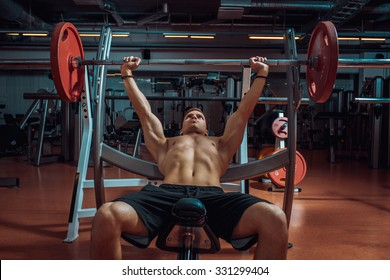 weight lifter lifting a barbell on an incline bench at gym