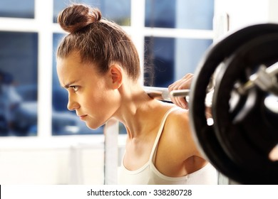 Weight lifting. The woman is picking barbell in gym