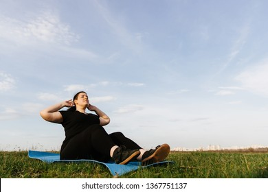 Weight losing, outdoor activity, exercising, healthy lifestyle. Overweight woman doing sit-ups on exercise mat outdoors.
