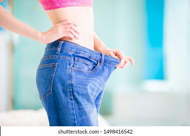weight loss concept of asian woman in her old big jeans