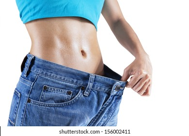 Weight loss concept: Slim woman pulling oversize jeans