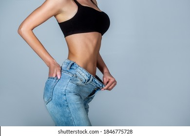 Weight loss concept. Thin woman in big pants, weight loss concepts. Slim girl wearing oversized pants. Woman shows weight loss. Dieting. Woman showing slim body after sport trainings, healthy eating.