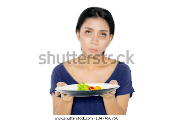 Weight loss concept. Young woman looks pale while holding a plate of small portion salad in the studio