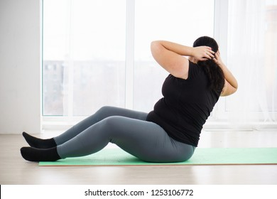 weight loss, fitness, sport, exercising, home workout, training and lifestyle. young plus size woman doing crunches on mat at home