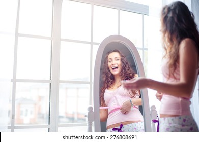 Weight loss. Happy young woman measuring her waist while looking at mirror at home.