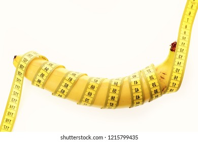 Weight loss and healthy food concept. Banana with yellow tape for measuring figure. Yellow tape around banana isolated on white background. Rolled centimeter ruler spinned around fresh fruit.