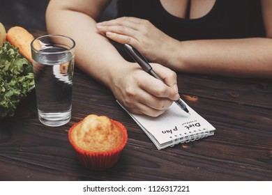 Weight loss, healthy lifestyle, diet and people concept. Close up of overweight woman writing diet plan into copy book